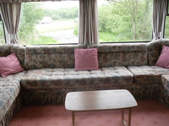 large lounge area with views towards Woody's Lake plenty of seating, tv, play station with games, dvds, board games, pull out sofa bed