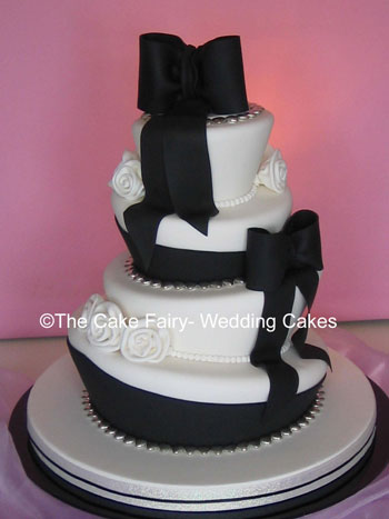 RW14 WONKY BOWS & ROSES    Wonky wedding cake with sugar bows and sash. Decorated with  sugar stylised roses