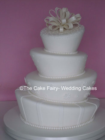 RW23  WONKY RUFFLE  Bridal white wonky wedding cake with subtle side decoration and top ruffle bow