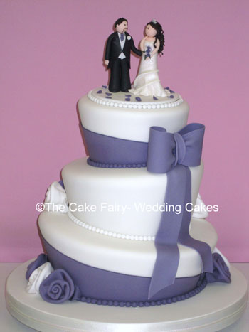 RW24  WONKY WEDDING DAY  Wonky wedding cake with large sugar bows and sashes topped by a sugar bride and groom