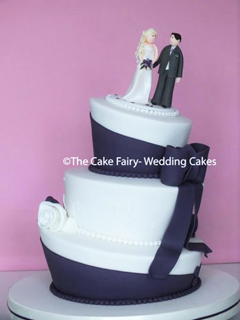 RW68 WONKY PURPLE WEDDING  Decorated in the Wedding colours with a large sugar bow and the Bridal couple on top