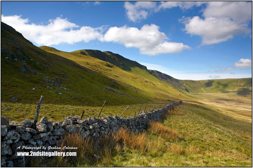 A dry stone wall and Mountains in Cadair Idris, with big white clouds and bright blue sky in the early morning sun