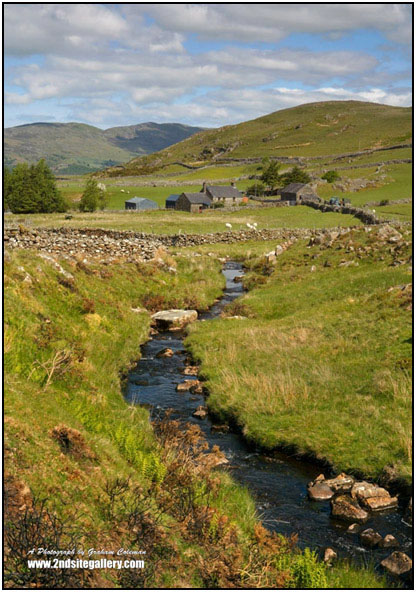 a sheep farm in the foot hills of cadair idris, a small stream in the foreground leads into the picture