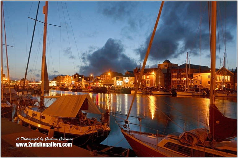Boats moored at Weymouth Harbour at night a photograph by Graham Coleman