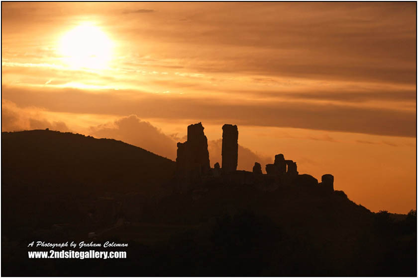 Corfe Castle Silhouette, view of the Sun setting behind Purbecks most famous landscape a photograph by Graham Coleman