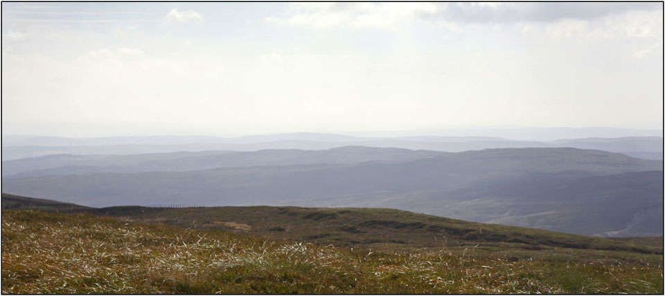 A panoramic view of across the mountains of north Wales in slightly misty conditions, taken from The Berwyn mountain range