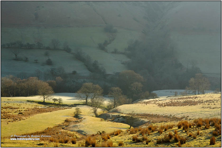 frosty morning landscape in the black mountains, trees and fields on the mountainside with the morning sun lighting up the foreground
