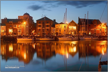 View of weymouth harbour lit up at dusk