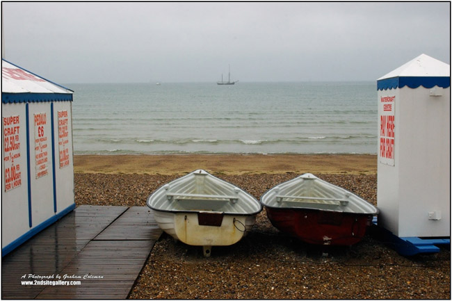 A view of Weymouth Beach on a very wet day with boats and stalls in the foreground