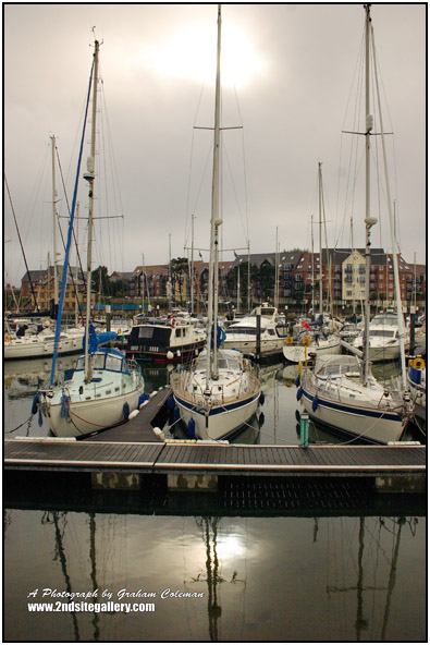 Boats moored at weymouth harbour on a very dull day with sun just breaking through the clouds