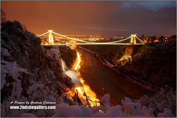 clifton suspension bridge illuminated at dusk in the snow