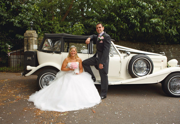 Wedding photograph the bride and groom infront of the wedding car