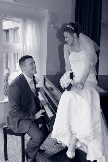 Posed Portrait of the groom serenading the Bride on a piano