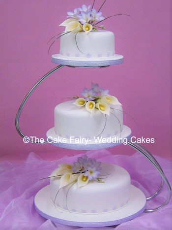 R39   HEARTS & FREESIAS    Wedding cake  set up on an offset stand.  Decorated with lilac sugar hearts and finished with handcrafted sugar arums and freesias.