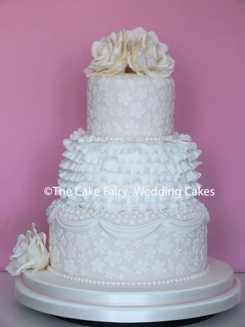 RS116 LACE + FRILLS  A very pretty ornate Wedding cake with sugar side designs and handcrafted roses