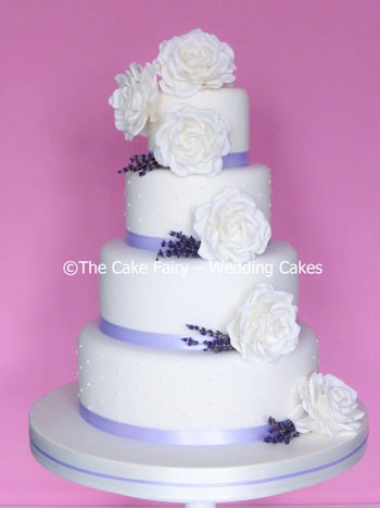RS145 LAVENDER BLUE 4 tiers of cake decorated with large sugar roses and dried lavender