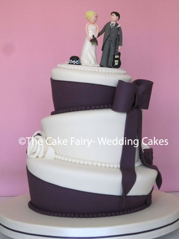 RW45 WONKY WPC    An elegant wonky Wedding Cake with a Bride + Groom topper plus their interests