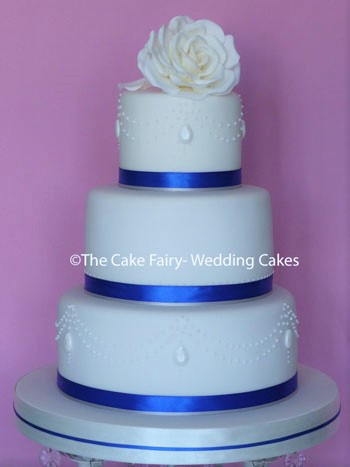 RS162 ROYAL BLUE POLKA ROSE   An  small 3 tier Wedding cake with a pretty royal iced dot design and a sugar rose