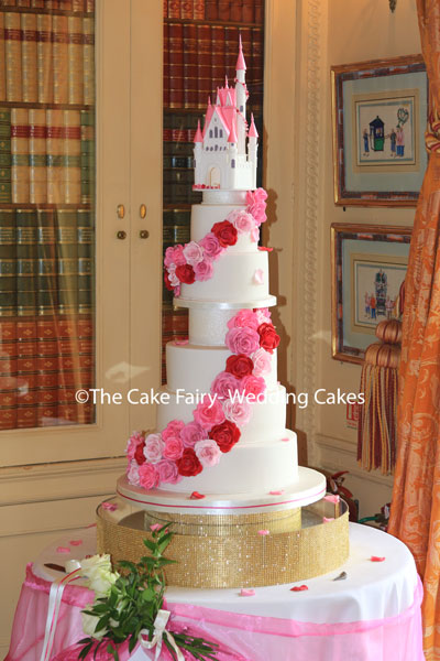 RS295 OPULANCE 5 deep tiers swathed with handcrafted sugar roses and finished with a bespoke sugar castle