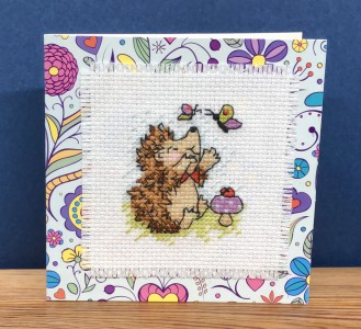 Hedgehog Card: Hedgehog 'playing with butterflies' in Cross Stitch
